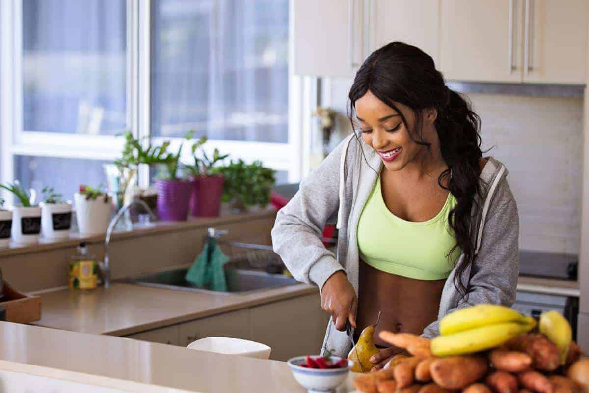 young woman in workout clothes cutting fruit in a kitchen with a pile of health foods nearby