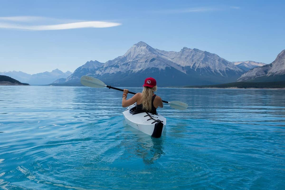 woman kayaking in mountain lake