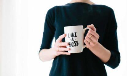 woman wearing black shirt holding white coffee mug that says like a boss