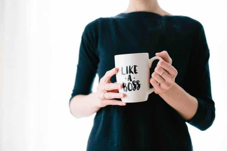 woman wearing black shirt holding white coffee mug that says like a boss