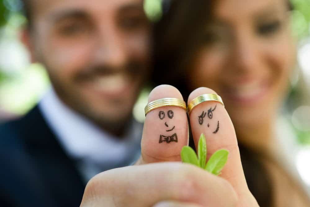 wedding rings on their fingers painted with the bride and groom, funny little faces