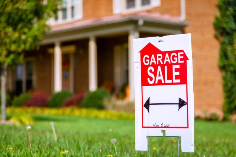 closeup image of garage sale lawn sign in front of orange brick house