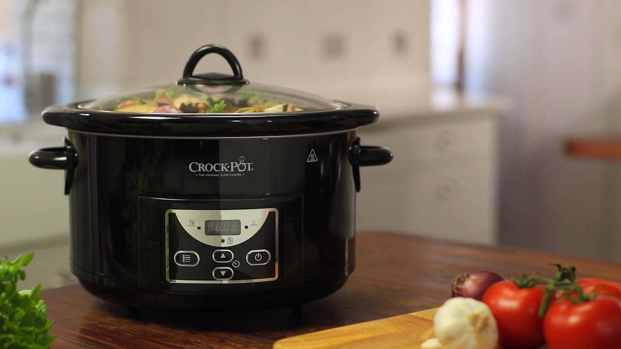 crockpot sitting on kitchen counter with vegetables nearby