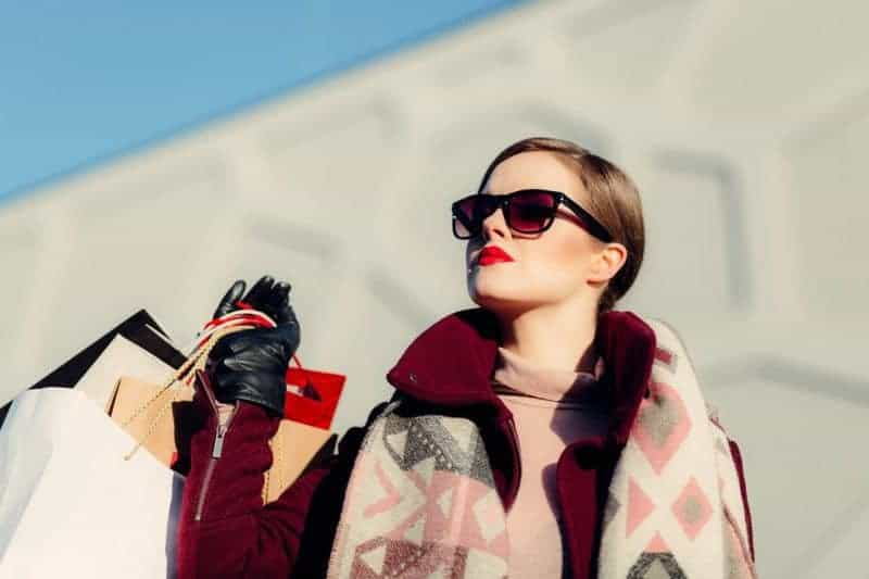 fashionable woman in red coat wearing sunglasses with a hand full of department store shopping bags