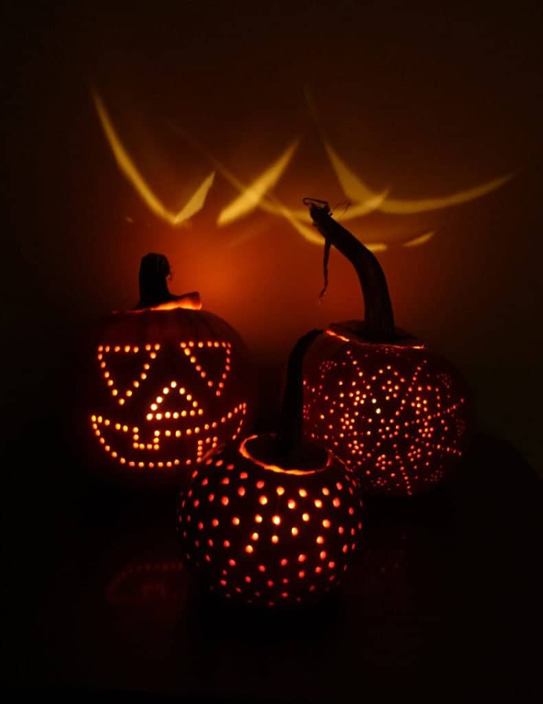 three lit up pumpkins in a dark room showing the drilling technique as a pumpkin carving idea