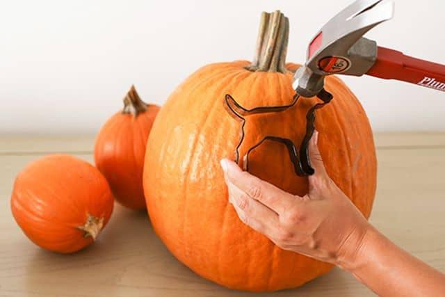 person hammering a dog metal cookie cutter into a pumpkin as a pumpkin carving idea
