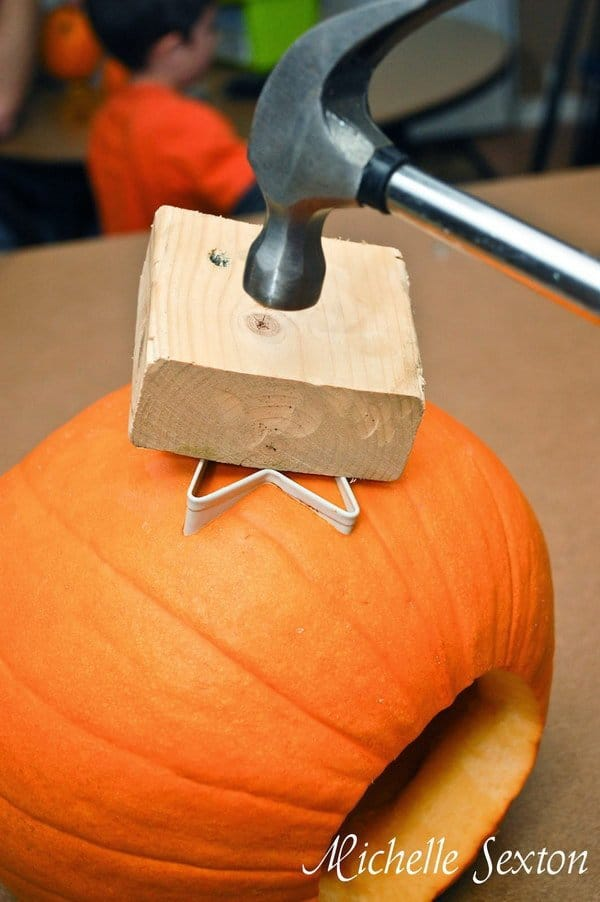 hammer over a small wooden block, used to hammer a star shaped cookie cutter into a pumpkin using the cookie cutter pumpkin carving idea