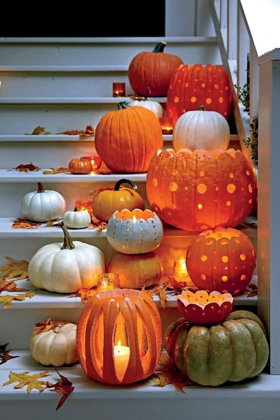 orange, white, and green lit pumpkins carved with polka dot patterns on a white front porch