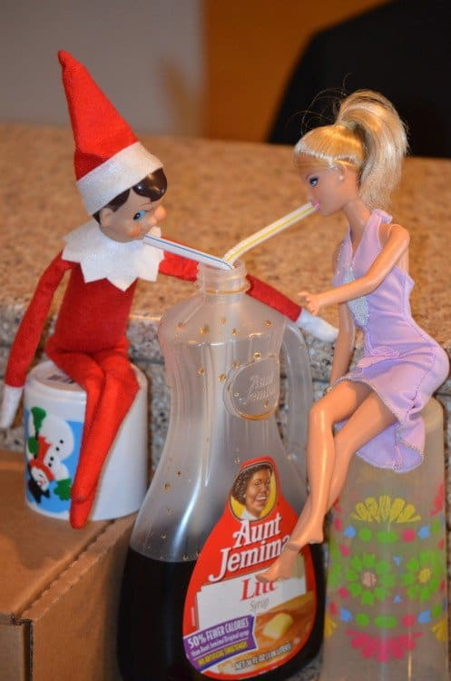 elf and Barbie drinking syrup out of the bottle with straws for date night elf on a shelf idea