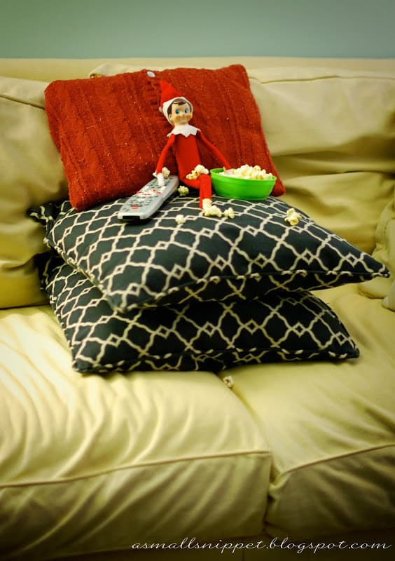 elf leaning on blanket sitting on pillows on couch with popcorn bowl and tv remote for movie night elf on a shelf idea