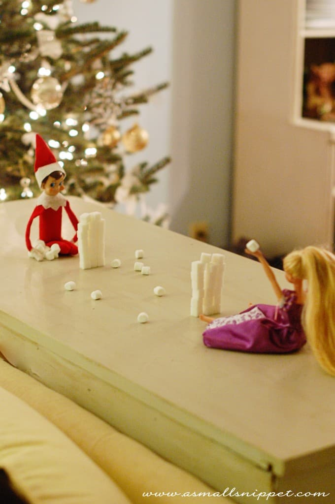 elf and Barbie with marshmallow stacks having a snowball fight for elf on a shelf idea for kids