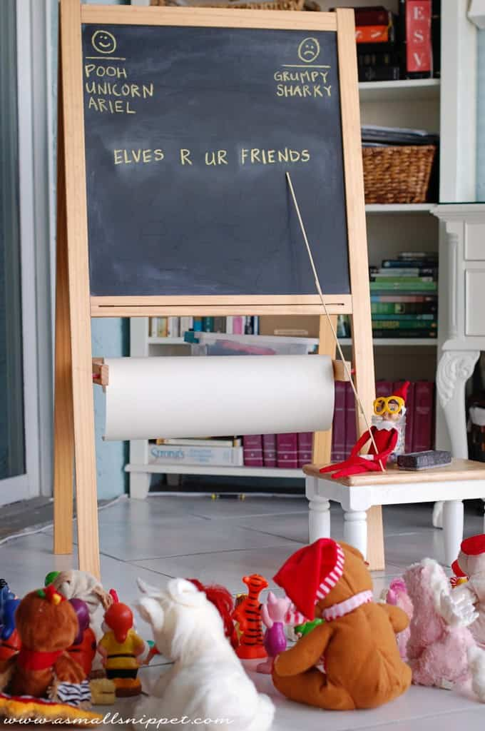 elf pointing to chalkboard to teach stuffed toys sitting on floor for elf on a shelf idea for teachers