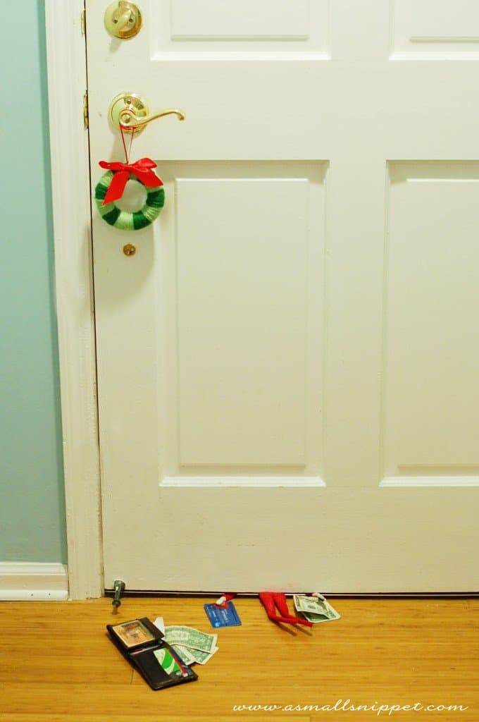 elf stuck under closed door with open wallet and money nearby for naughty elf on a shelf idea