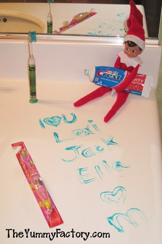 elf holding toothpaste near toothbrush on bathroom counter with words written in toothpaste