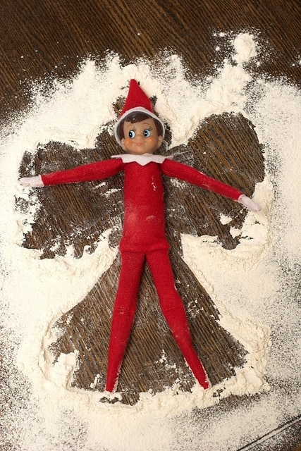 elf making a snow angel in spilled flour for naughty elf on a shelf idea