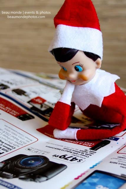 elf looking at store advertisement for shopping elf on the shelf idea