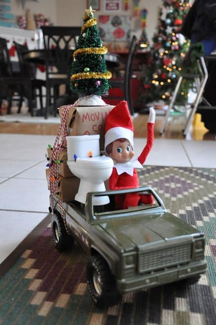 elf driving toy truck with toy toilet and boxes tied to the truck for elf on a shelf leaving going back to North Pole