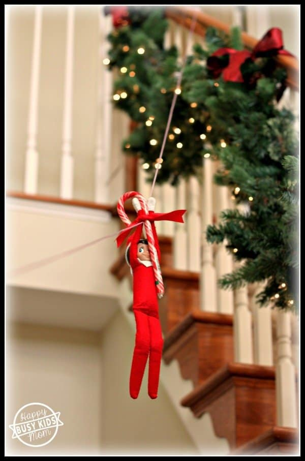 elf zip lining with candy cane from stair banister for mischievous elf on a shelf idea