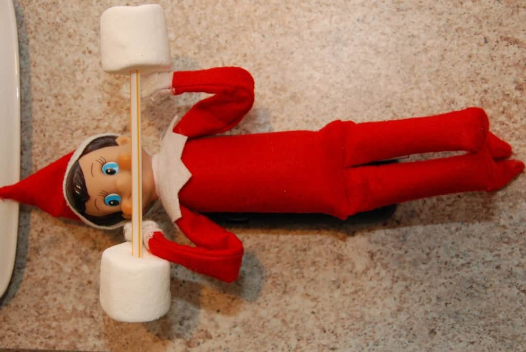 elf holding weight bar made from straw and marshmallows for fitness elf on a shelf idea