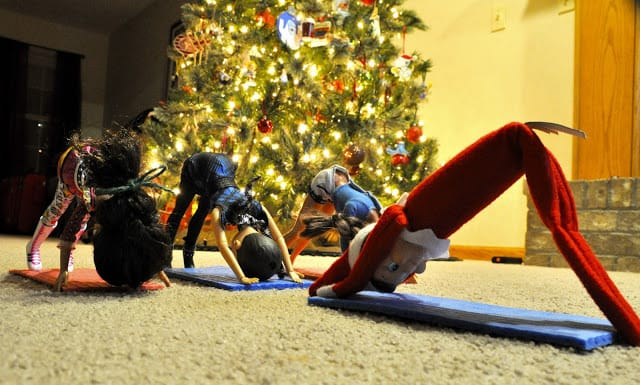elf and other toys doing yoga in front of Christmas tree for fitness elf on a shelf idea
