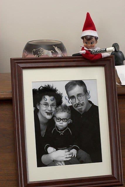 elf holding marker near defaced family photo for naughty elf on a shelf idea