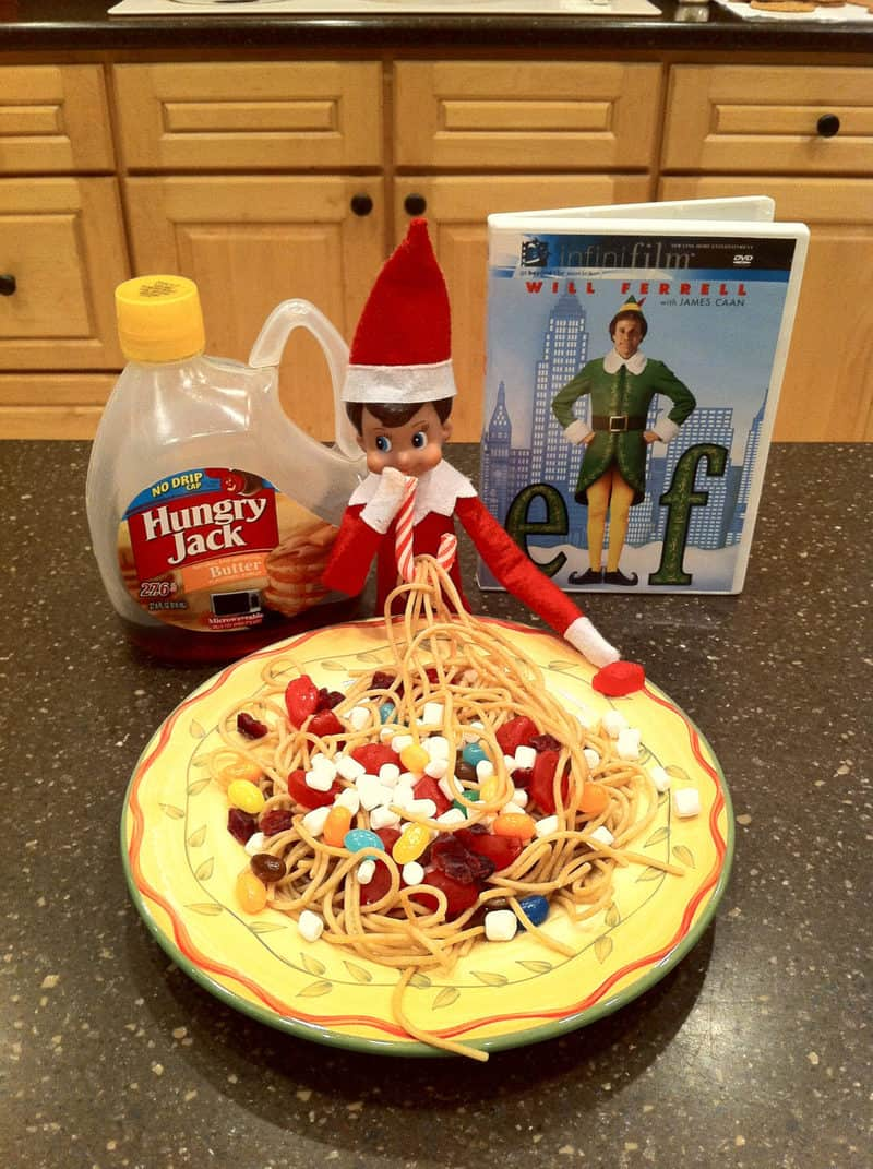 elf on kitchen counter eating from plate of spaghetti and candy with syrup and elf movie case