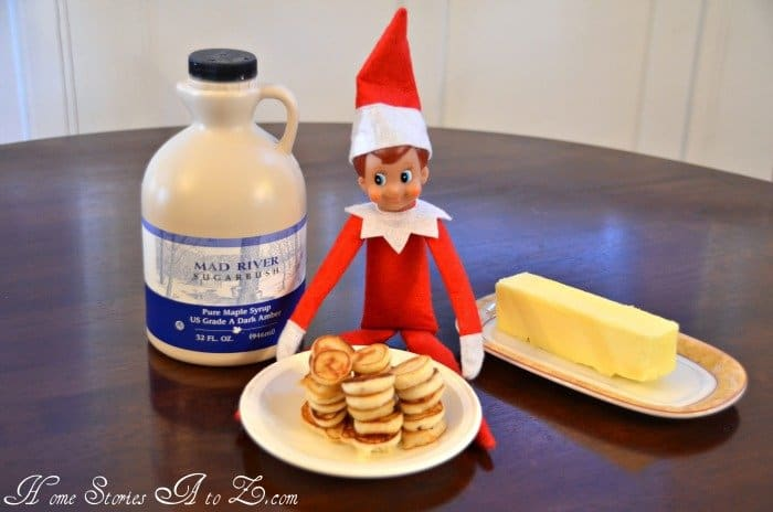 elf with mini pancakes on a plate syrup and butter sitting on kitchen table