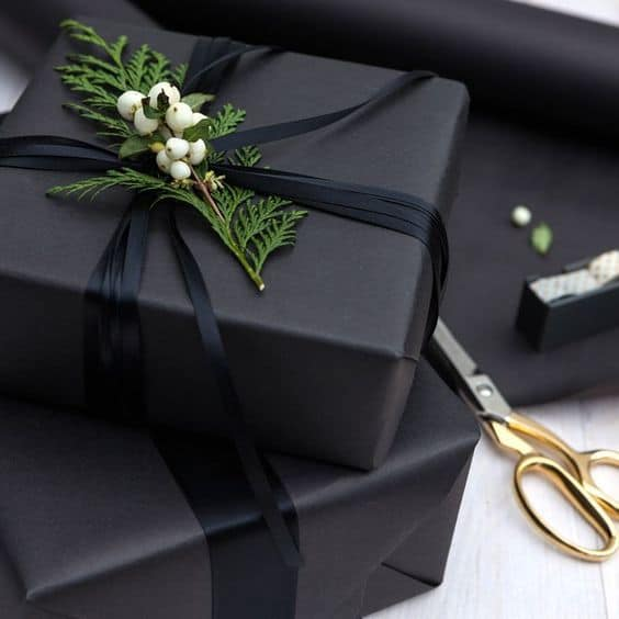 chic and coordinated black wrapped gifts with black ribbons and sprig of fresh foliage for a unique and beautiful gift wrapping idea