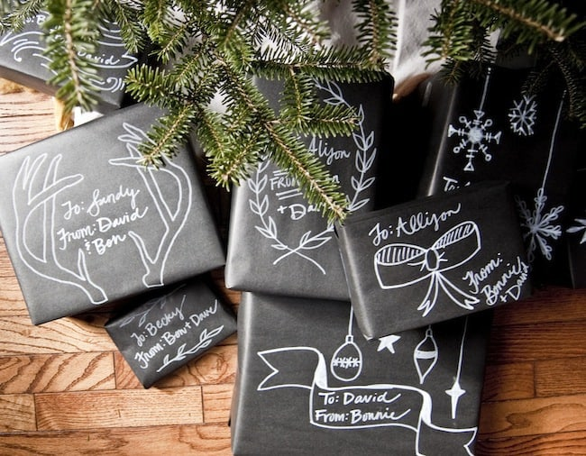 black craft paper wrapped gifts with white marker decorations and labeling for a unique gift wrapping idea