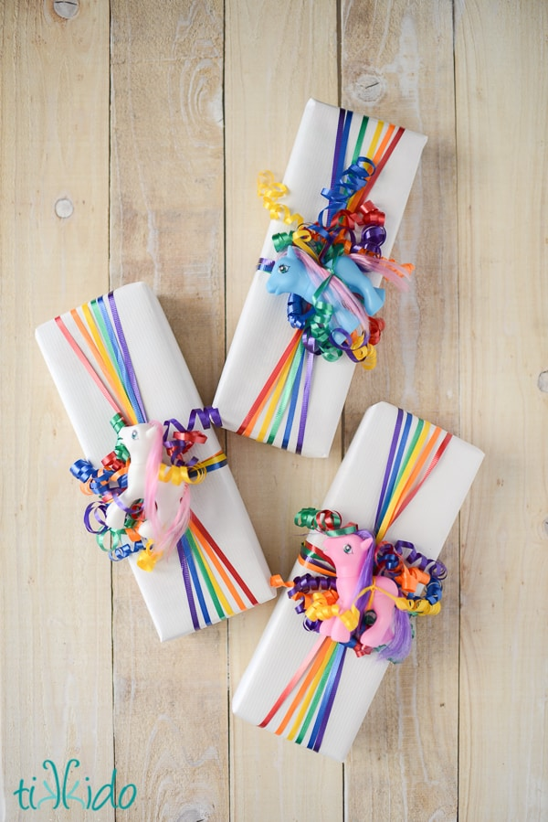 white paper wrapped gifts with flared rainbow ribbons and small toy pony for unique gift wrapping idea for little girls