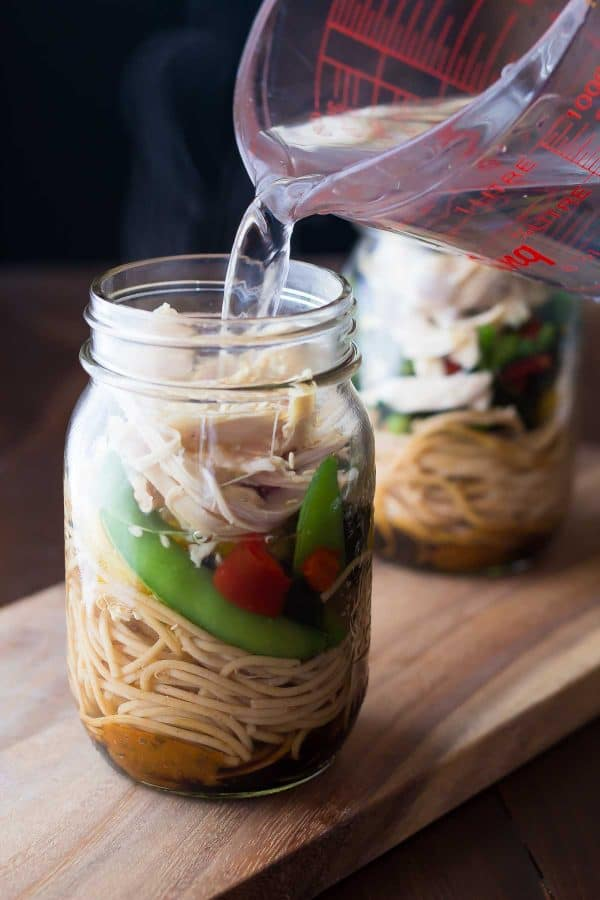 pouring water into a mason jar with healthy homemade instant noodles meal prep idea