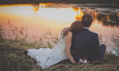 newlyweds sitting snuggled watching sunset over a pond