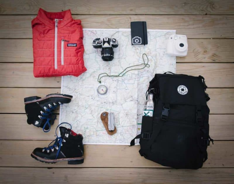 map, cameras, backpack, and outerwear gear