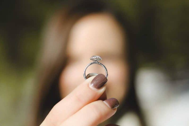 woman holding up diamond engagement ring