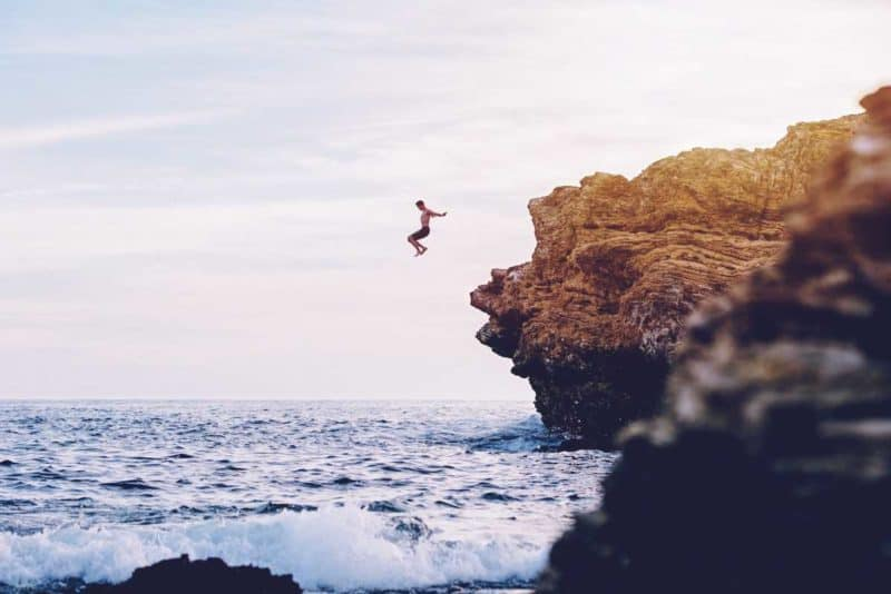 man jumping off a rock outcrop into the ocean