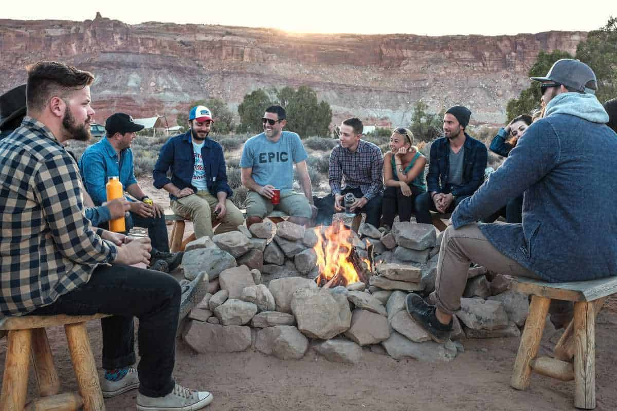 friends smiling around campfire in a rocky landscape