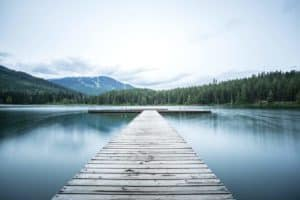 long dock stretching out into serene lake surrounded by mountains and pine trees