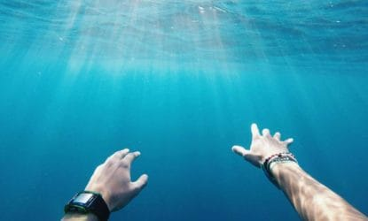 outstretched hands of underwater swimmer