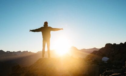 person standing on mountain top with outstretched arms watching the sunrise