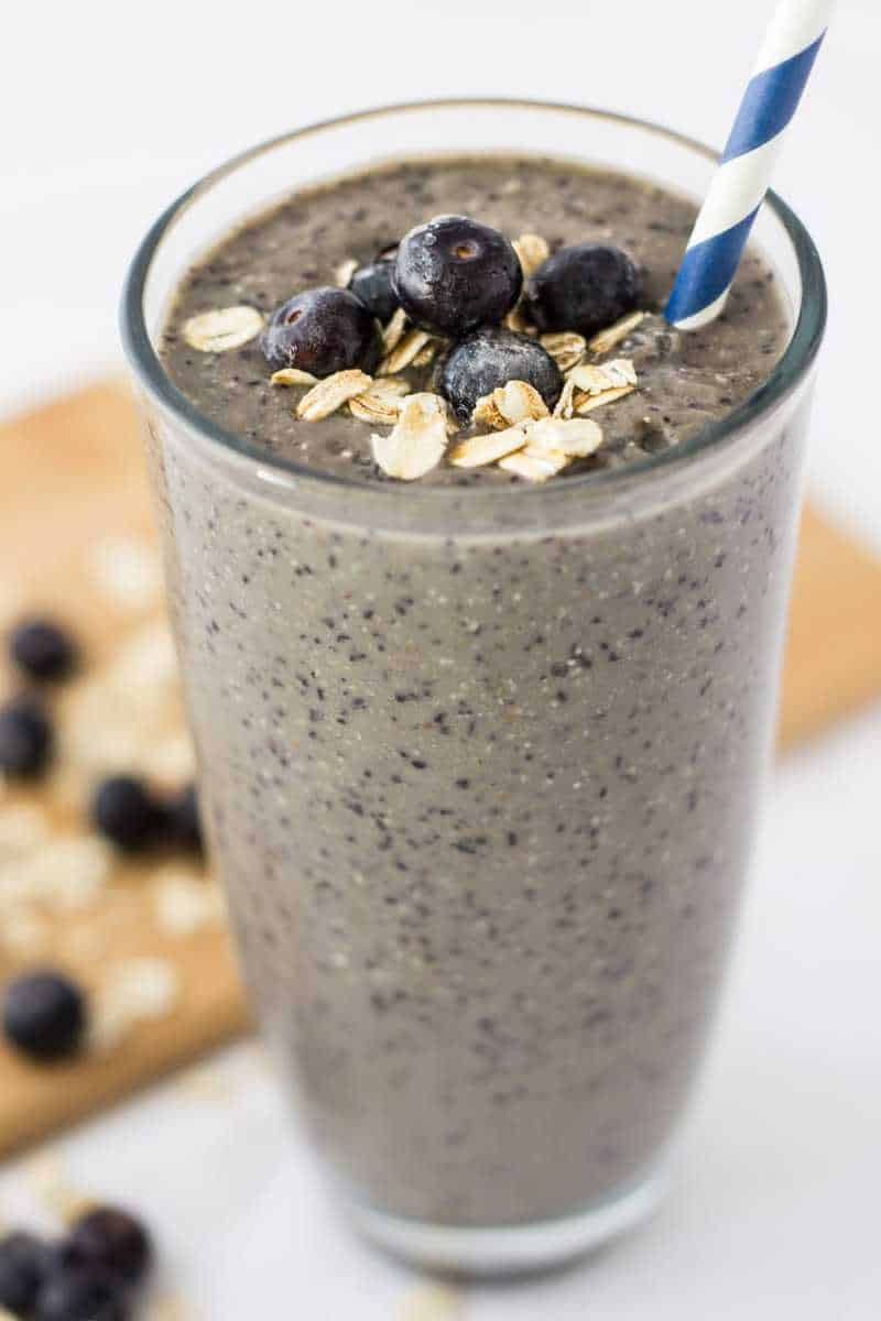 frosty glass full of blueberry oatmeal weight loss smoothie topped with oats, blueberries, and a blue straw