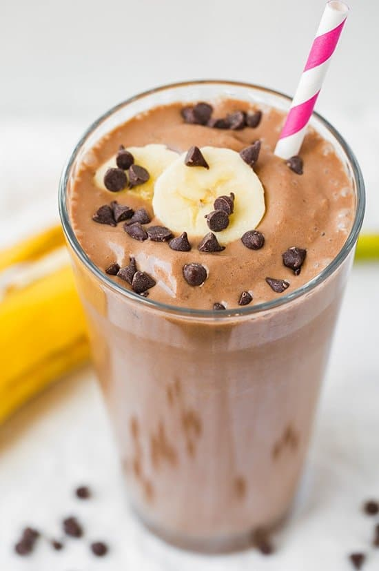 chocolate colored smoothie with pink straw topped with banana slices and mini chocolate chips