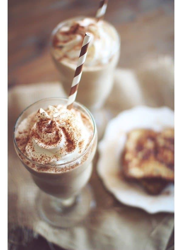 looking down at stemmed glass with French toast smoothie topped with whipped cream, cinnamon, and a straw with blurred plate of food in background.