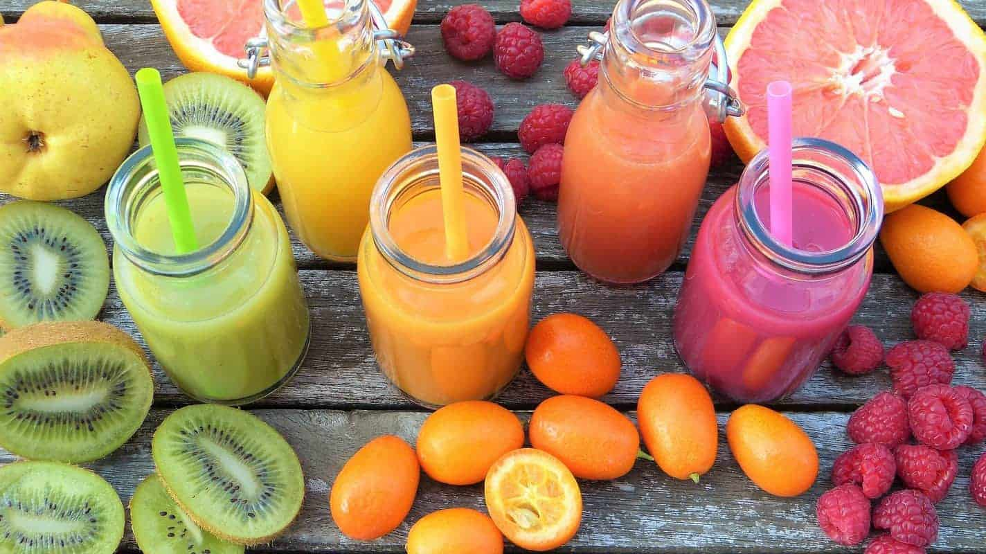 colorful smoothies and fruits on a wood table