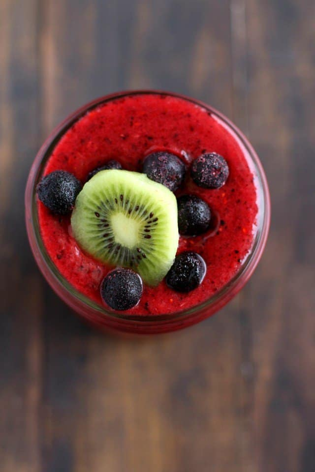 aerial view of a red smoothie topped with kiwi slice and blueberries
