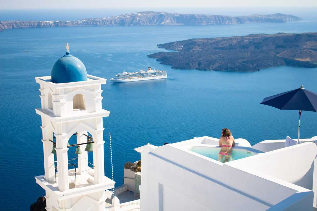 white and blue buildings of Greece overlooking large ship on the sea