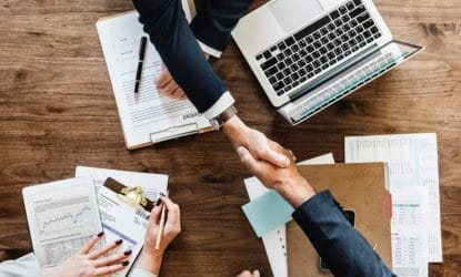 men shaking hands over work reports and laptop, woman taking notes nearby