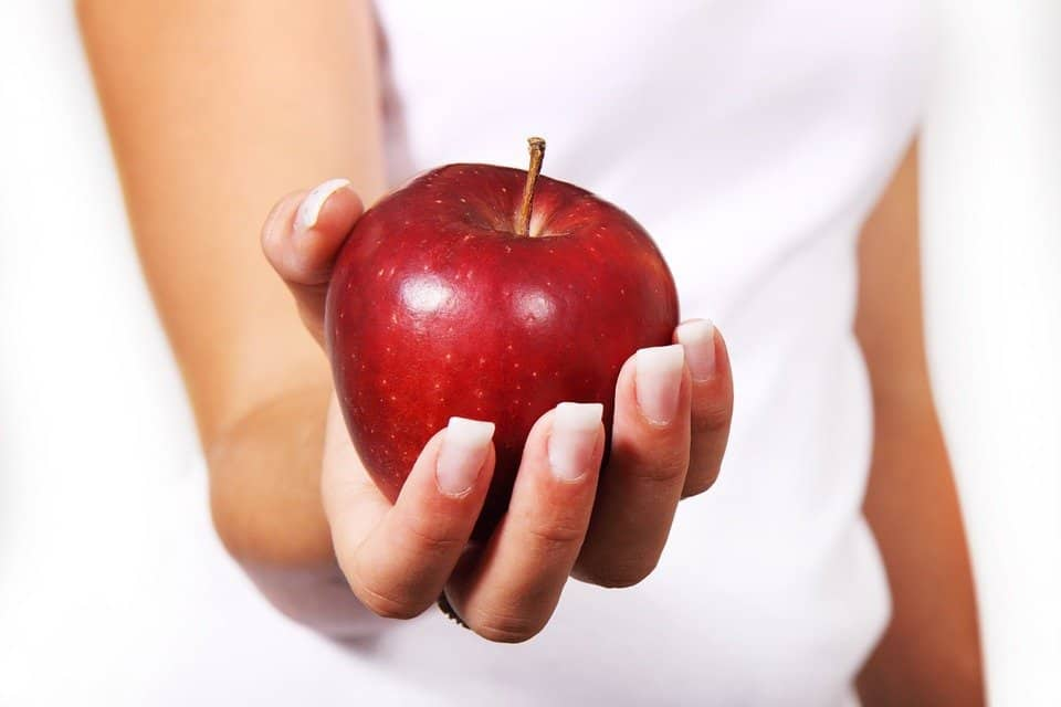 woman's hand holding a shiny red apple