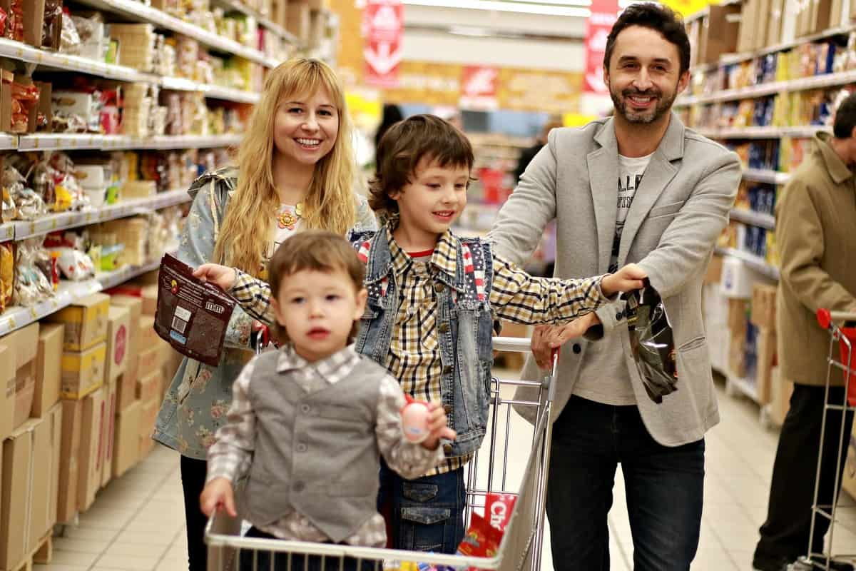happy family with two boys in the shopping cart, in an aisle of the store while grocery shopping