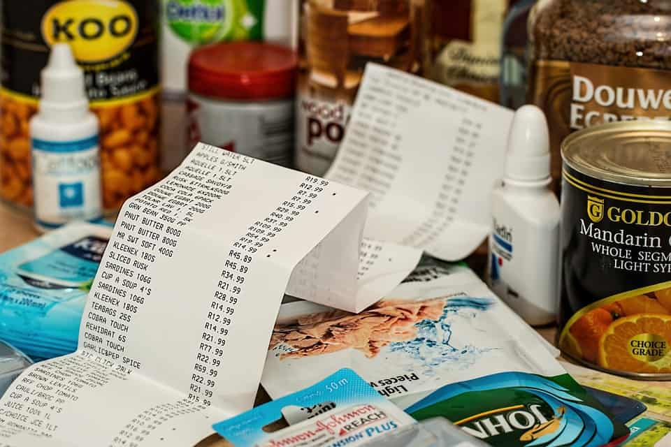 unfolded grocery receipt laying in a collection of smaller grocery items