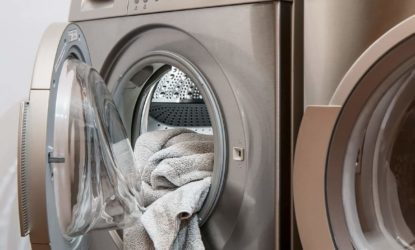 washing machine with towels hanging out of the door